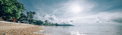 Tropical utterance landscape. Sea coast at sunrise. The sun rises over a sandy deserted beach on a tropical island.