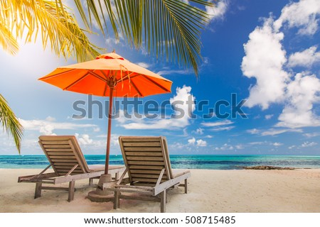 Tropical vacation background with sun beds and sun umbrella under the palm trees in sunlight. Idyllic beach scene - Shutterstock ID 508715485
