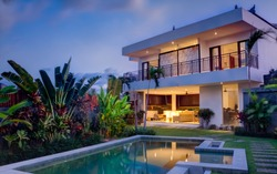 Tropical villa view with garden, swimming pool and open living room at sunset