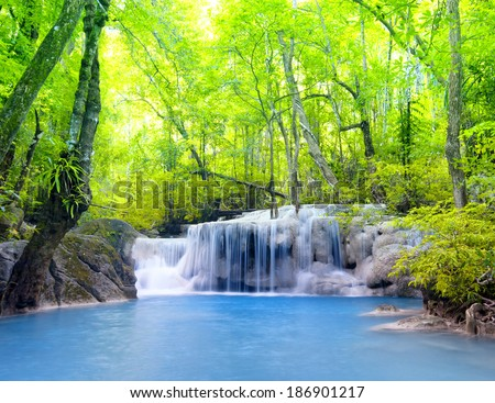 Tropical waterfall in Thailand, nature photography. Fresh water mountain river in wild green jungle forest. Scenic and peaceful Asia nature background of beautiful blue water pool and creek cascade  #186901217