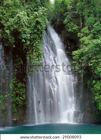 Tropical waterfall with pond in a pristine rain-forest and jungle setting. Tinago Falls near the City of Waterfalls, Iligan, Mindanao, Philippines