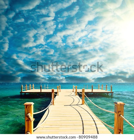 tropical wooden pier in turquoise sea stormy weather