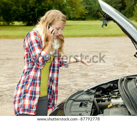 trouble with the car engine in the road, young woman phoning to help