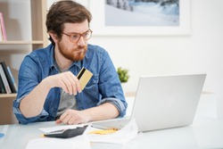 Troubled bearded guy holding credit card and using laptop