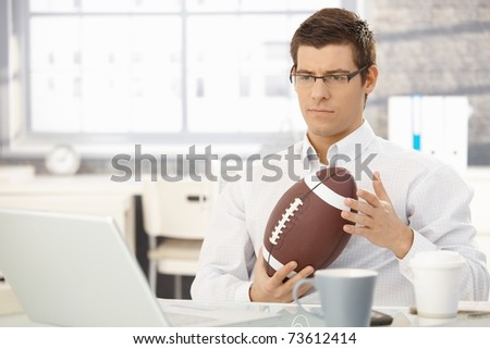 Troubled businessman thinking about work playing with football handheld in office.?