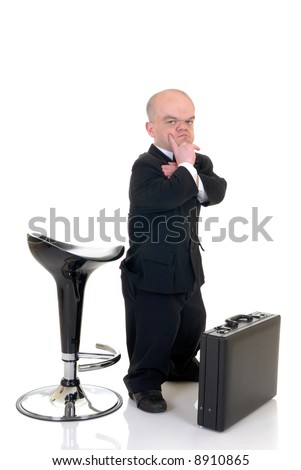 Troubled little businessman, dwarf in a formal suit with bow tie next to bar stool and suitcase, studio shot, white background