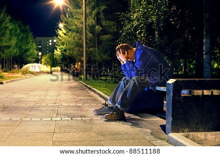 troubled teenager with hidden face sitting in the night park