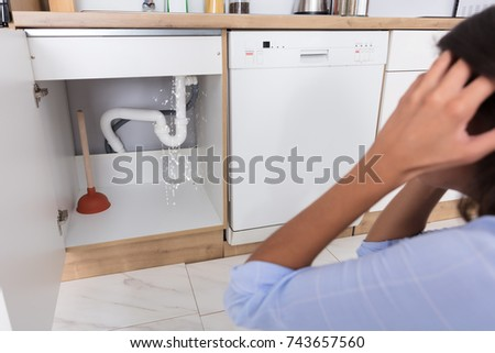 Troubled Woman Looking At Leaking Sink Pipe In Kitchen #743657560
