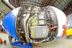 Troubleshooting the engine with an open hood of the aircraft in the aircraft hangar, mechanical repair close up view, checking all systems