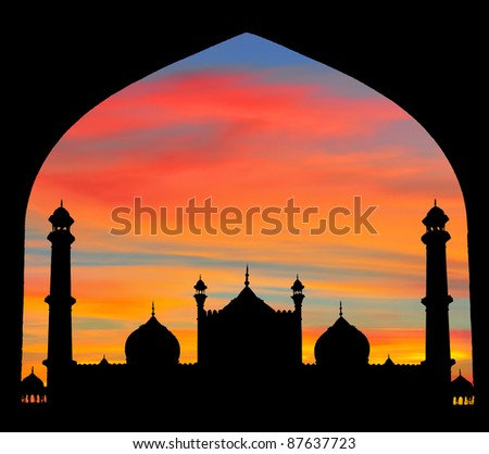 Trough a Mogul design arch, silhouette of great mosque of Old Delhi, India, at sunset.