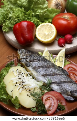 Trout in traditional restaurant setting, served with sliced potatoes,lemon and plenty of vegetables
