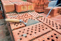 trowel for applying cement between bricks while constructing a building wall, close-up of brickwork construction work, nobody.