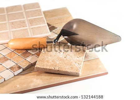 Trowel, marble and ceramic tiles on white background