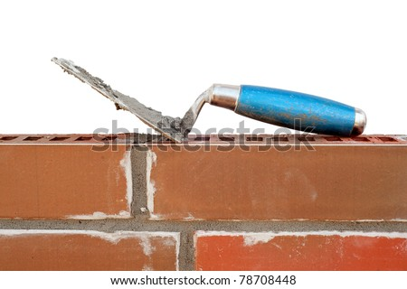 Trowel on new brick wall isolated on white