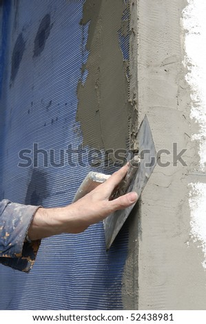 Trowel spreading mortar  on styrofoam insulation of wall