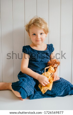 Trubschachen, Switzerland - December 16, 2019: Pretty caucasian little girl with short fair hair in blue dress holds her lovely barbie toy, sits in bright baby room and smiles