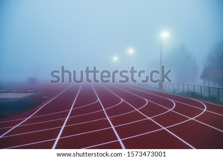 Truck and Field concept photo. Red athletics track in morning mist. Running photo, white edit space