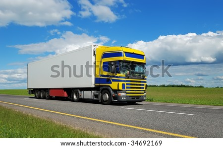 Truck (blue-yellow cabin) and white trailer moving on highway over bright sky. #34692169