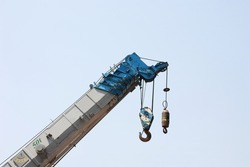 truck crane with hooks and scale weight on background is blue sky.