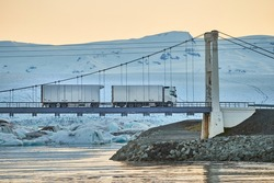 Truck crossing a bridge over an icy lagoon in Iceland