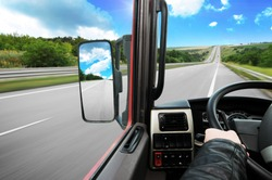 Truck dashboard with driver's hand on the steering wheel and side rear-view mirror on the countryside road against blue sky with clouds