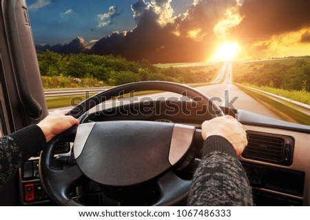 Truck dashboard with driver's hand on the steering wheel on the countryside road in motion against night sky with sunset