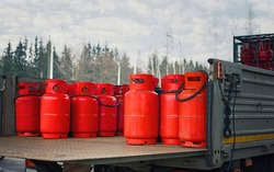 Truck deliver hazard goods, carrying red cylinders with compressed gas to customers. Delivering gas cylinders.Truck carrying gas cylinders.