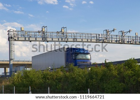 Truck drive under the highway toll gate, lorry in motion. Transportation on paying motorway