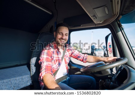 Truck driver driving his truck and changing radio station to play his favorite music. Trucker enjoying his job. Transportation services.