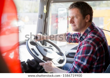 Truck driver driving in cab of semi-truck