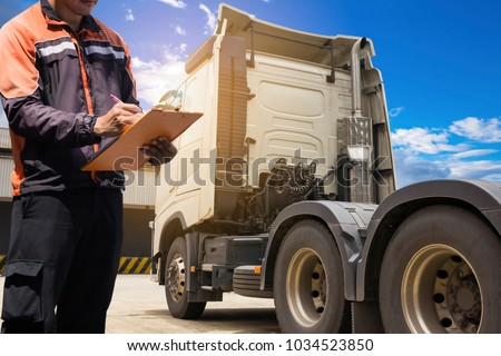 Truck driver hand holding clipboard writing and check list of engine truck.
