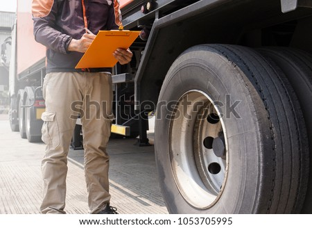 Truck driver holding clipboard with writing for safety checks of tire truck.