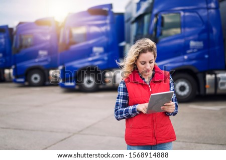 Truck driver holding tablet and checking route for new destination. In background parked truck vehicles. Transportation service.