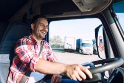 Truck driver job. Middle aged trucker driving truck. Professional middle aged truck driver in casual clothes driving truck vehicle and delivering cargo to destination. Transportation service.