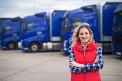 Truck driver occupation. Portrait of woman truck driver in casual clothes standing in front of truck vehicles. Transportation service.