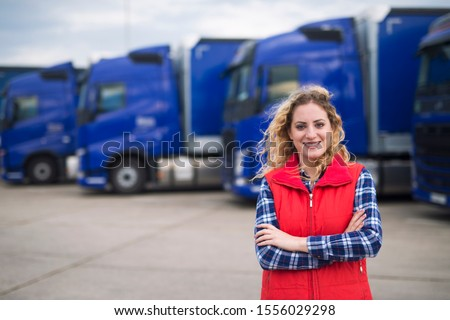 Truck driver occupation. Portrait of woman truck driver in casual clothes standing in front of truck vehicles. Transportation service. Foto d'archivio ©