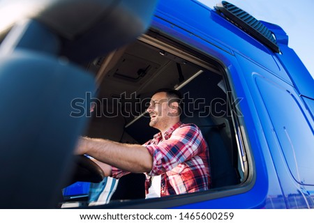 Truck driver occupation. Professional middle aged trucker in cabin driving truck and smiling. Transportation industry.
