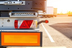 Truck driver semitrailer rear view, warning lights and long length signs on the trailer. Concept of safety and recreation at truck parking lots, sunset, copy space for text, commercial
