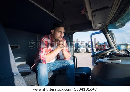 Truck driver sitting in his cabin and thinking about his family. Trucker missing his family being sad. Truck driver lifestyle. #1504101647