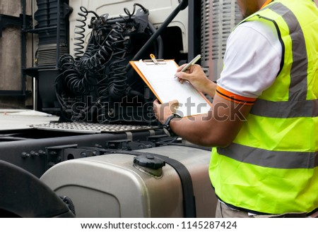 Truck driver writing  on a clipboard with checks repairing a truck