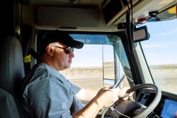 Truck drivers big truck driver holds the phone in cabin of modern truck vehicle on highway