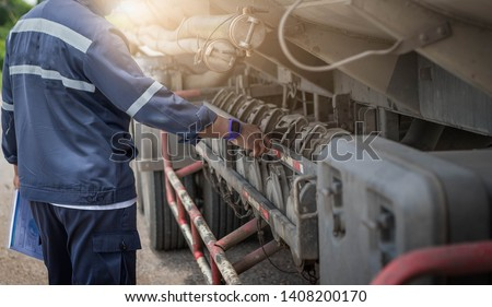 Truck drivers inspect order products in clipboard,Driver writing  in clipboard,Preforming a pre-trip inspection on a truck,preventive maintenance,spot focus. Imagine de stoc ©