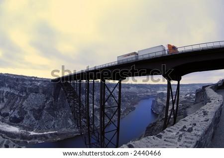 Truck driving over long bridge spanning a ravine