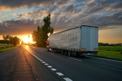 Truck driving toward the setting sun on the road in the countryside