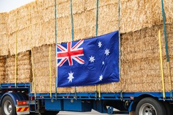 Truck filled with hay bales being transported to Aussie farmers in drought with Australian flag attached to the side