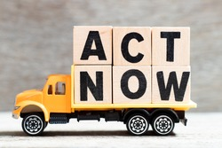 Truck hold letter block in word act now on wood background