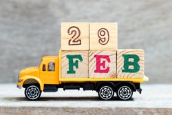 Truck hold letter block in word 29feb on wood background (Concept for date 29 month February , leap day)