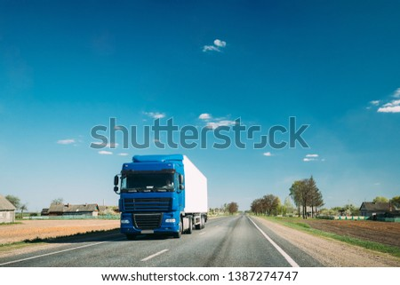 Truck In Motion On Country Road. Tractor Unit, Prime Mover, Traction Unit In Motion On Countryside Road In Europe. Business Transportation And Trucking Industry Concept