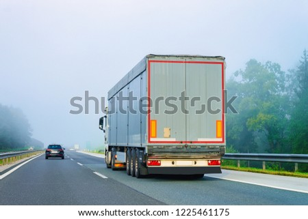 Truck in the asphalt road of Poland in a foggy weather. Lorry transport delivering some freight cargo. #1225461175