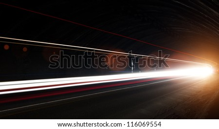 Truck light trails in tunnel. Art image with lens flares . Long exposure photo taken in a tunnel